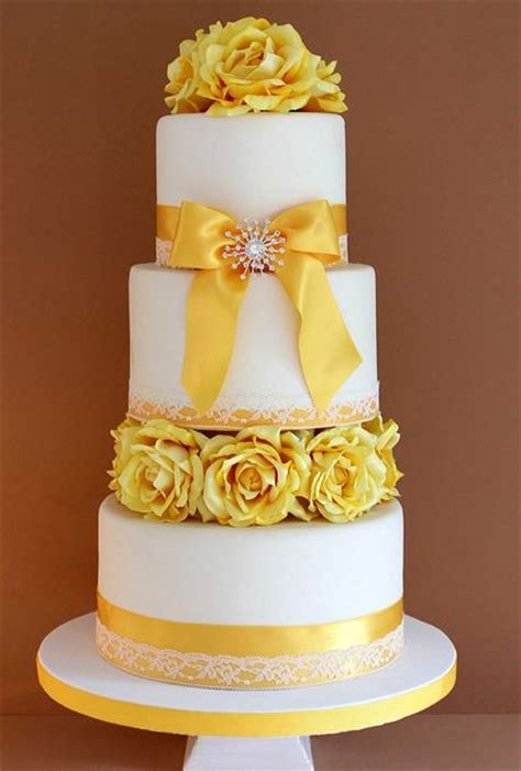 three tier white wedding cake with yellow flowers and ribbons jpg 1 comment