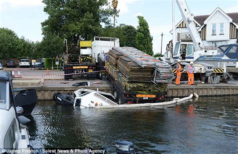blue boat house car park lorry laden with scaffolding rolls off the edge of marina