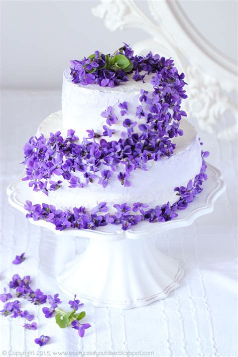 Pretty white tiered cake with cascading purple flowers