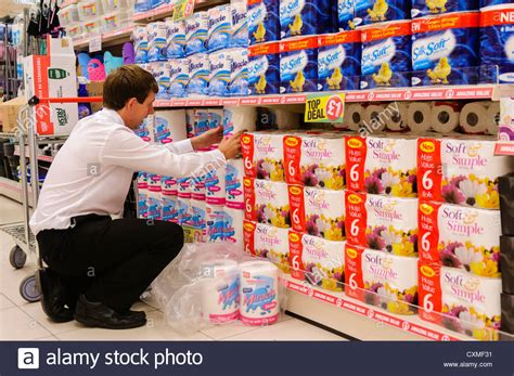 Shelf Shopping by Store Manager Assists In Stacking Shelves In A Poundland