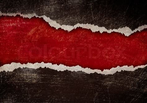 Red hole with torn edges in black grunge paper   Stock