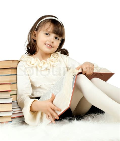 small teen the cute little girl lie with textbook and happy smile on