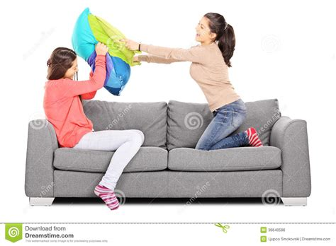 two girls having on couch two young girls having a pillow fight seated on sofa