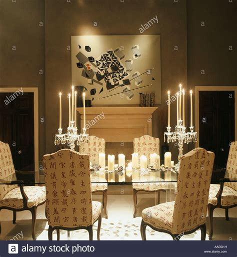 Dining Table Candles Glass Dining Table With Upholstered Chairs Lit By Candles And Artwork Stock Photo Royalty Free