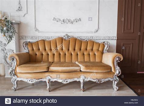 cornici di design soggiorno con antico ed elegante divano beige su bianco di