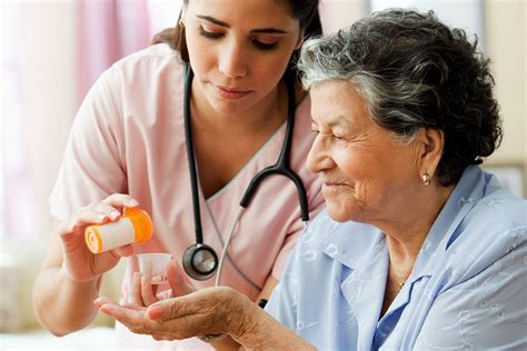 hispanic helping senior with medication one