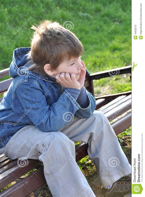 pensive boy sitting   park bench stock  image