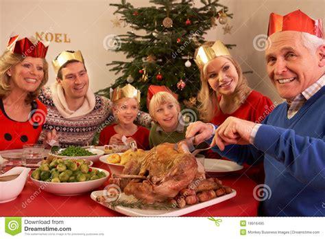 three generation family enjoying christmas meal stock