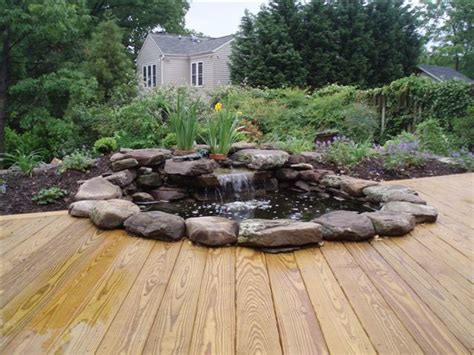 waterfall pond with wood stained deck contemporary patio dc metro by cbell ferrara