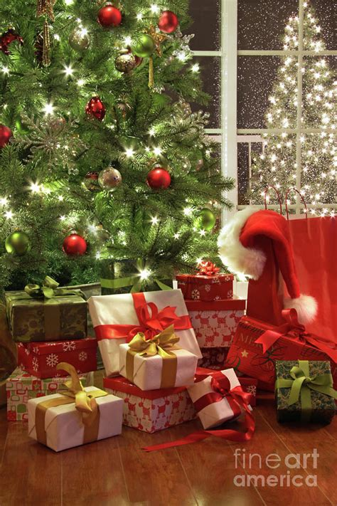 brightly lit christmas tree with lots of gifts by sandra