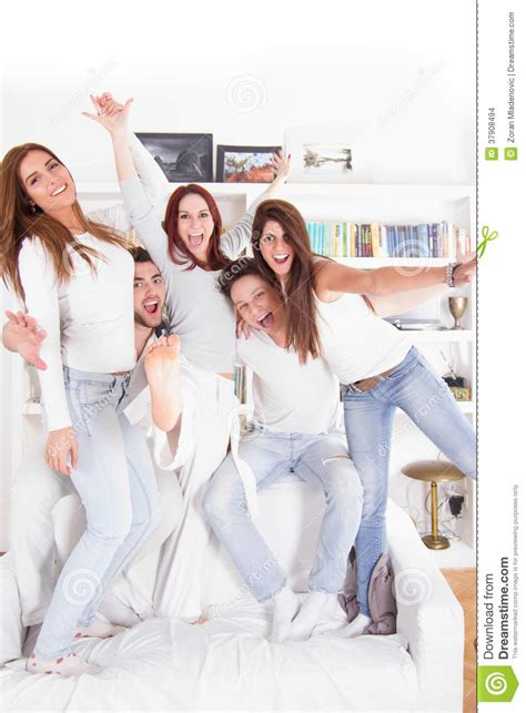 standing on the couch friends standing on the couch smiling indoors stock images