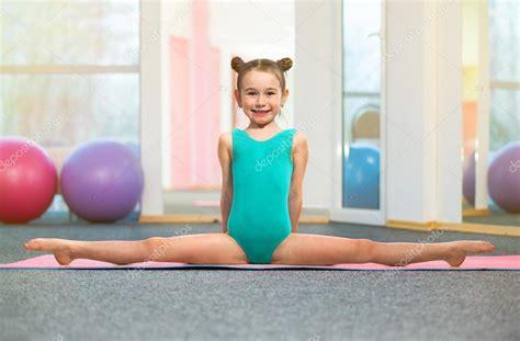 gymnastic little girl little girl gymnast sitting in the cross split in gym