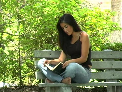 bench latin a beautiful young barefoot latina relaxes on the ground with a blanket and a book she