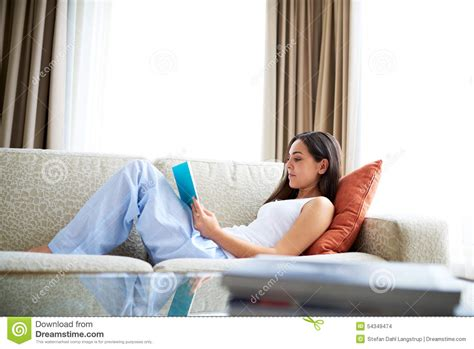 woman reclining woman reclining against orange cushion on couch stock