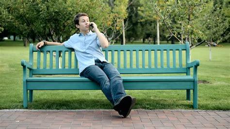 man sitting on bench senior man talks on phone elderly male on park bench