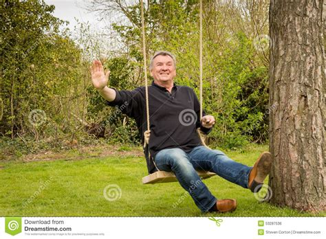 swinging man senior man on a tree swing in the garden stock photo