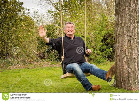 swinging seniors senior man on a tree swing in the garden stock photo