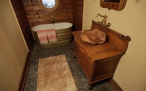 stock tank bathtub hobbit hole tiny house covered with dirt and living roof