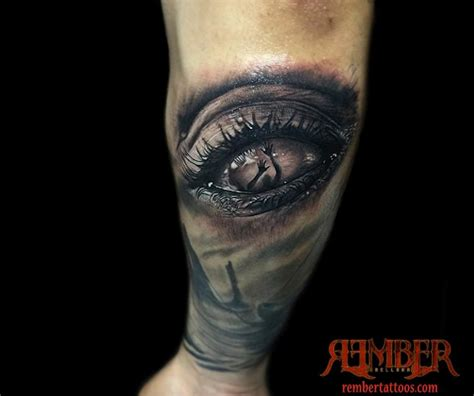 black tattoo hyperrealism eye done in black and grey by rember