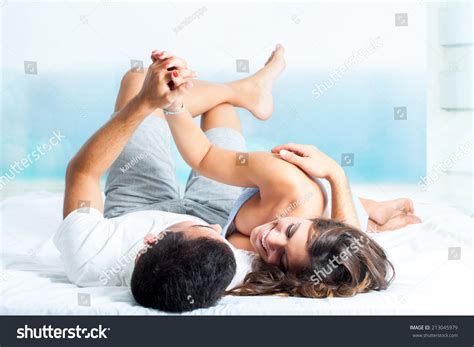 laying on my bed young laughing couple laying on bed holding hands stock