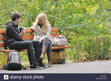 people sitting on bench two young people sitting on bench in park and have a