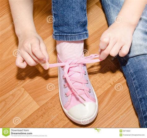 kid tying shoes child tying shoes sitting on the floor stock photo