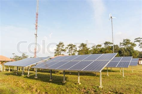 solar panels and wind turbine on green grass with blue sky