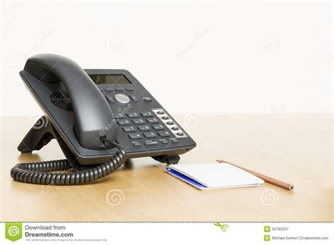 free desk phone phone on desk with notepad on wooden desk royalty free