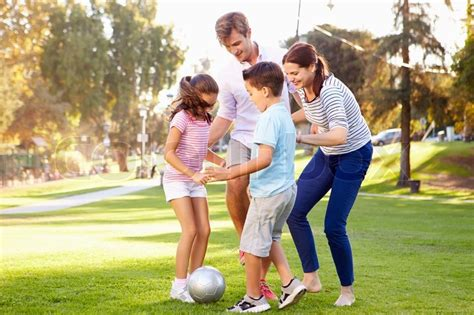 family playing soccer  park  stock photo
