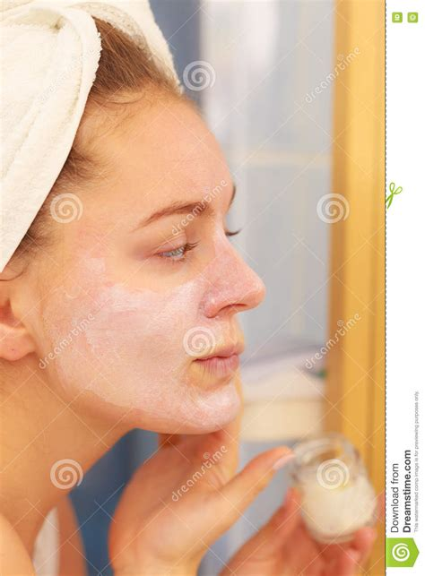 bathroom facial woman applying mask cream on face in bathroom stock