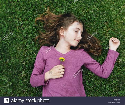10 year old a ten year old girl lying on the grass with her eyes