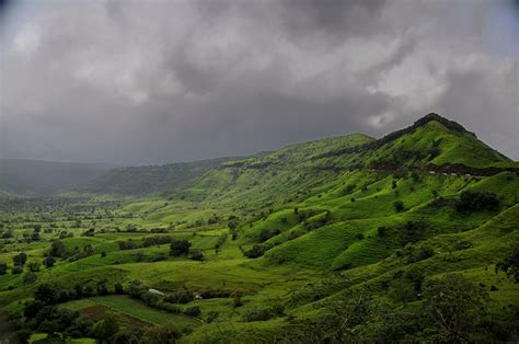storm clouds gather   lush green hills