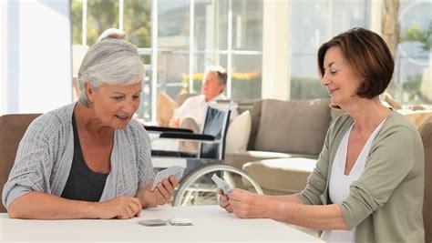 elderly friends cards together in a nursing