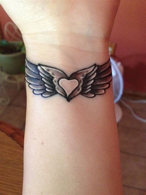 wings tattoo on wrist my wing with a in the middle my style