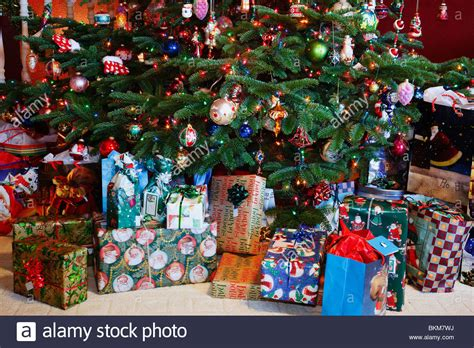 a christmas tree with gifts underneath it stock photo