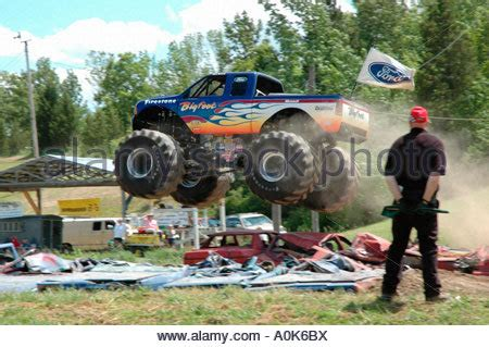 Monster Truck Jumping Over Crushed Cars In A Race Stock