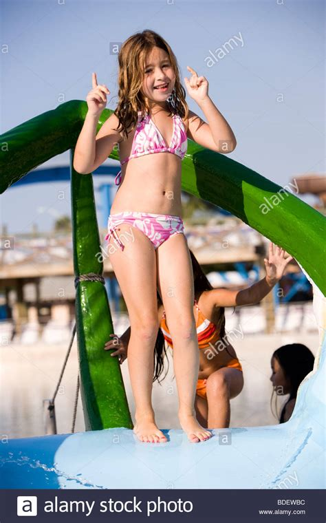 girl dancing on boat with kid little girl standing on top of water slide dancing stock