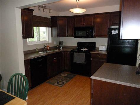 cherry cabinets pergo floor black appliances  kitchen