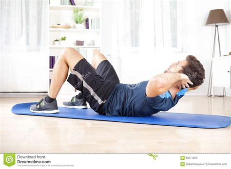athletic doing curl ups exercise at home stock photo