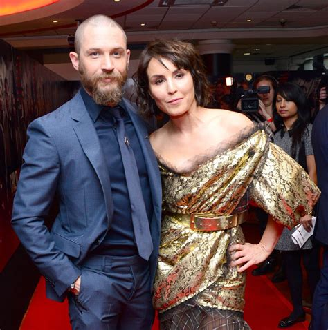 noomi rapace and tom hardy cuddle up to cute puppy while tom hardy in well tailored suit with noomi rapace at the