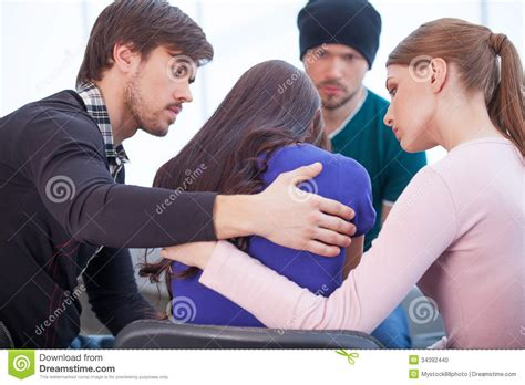 how to give a comforting hug group of people comforting upset woman stock photo