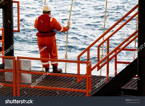 a rig worker holding a swing rope while waiting for a vessel in order to be transported to a
