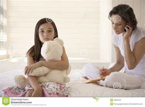 4 Bedroom House Plans South Africa mother using cellphone with daughter holding teddy sitting