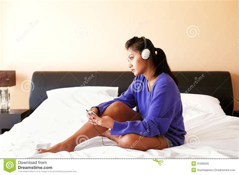 free music beds young woman in headphones listening to the music in bed royalty free stock photo
