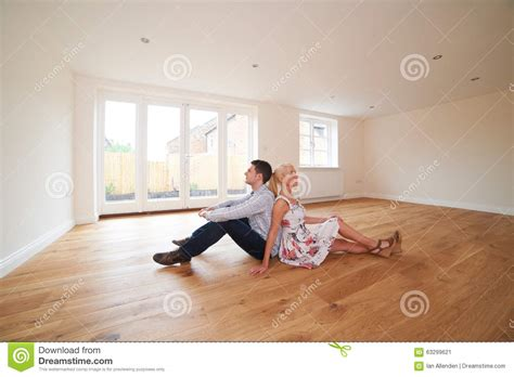 young couple room young couple sitting in empty room of dream house stock