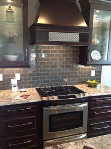 espresso kitchen cabinet with frosted glass door and dark light gray long subway backsplash tile