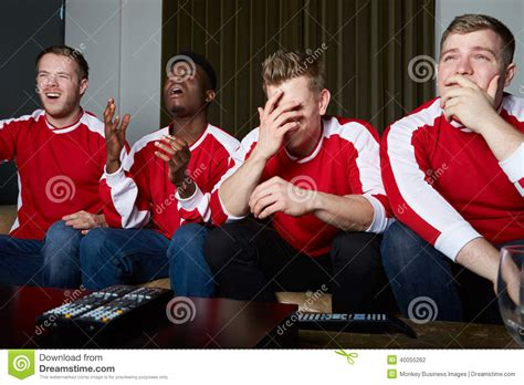 type of sport that fans watch on tv on thanksgiving group of sports fans watching game on tv at home stock