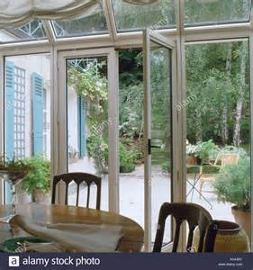 Dining Room French Doors stock photo glass french doors in conservatory dining room with view