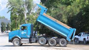 A Yard Of Gravel Blue Kenworth Dump Truck Slowly Dumping His Load Of New