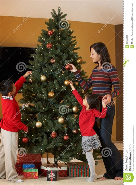 mother and children decorating christmas tree stock image